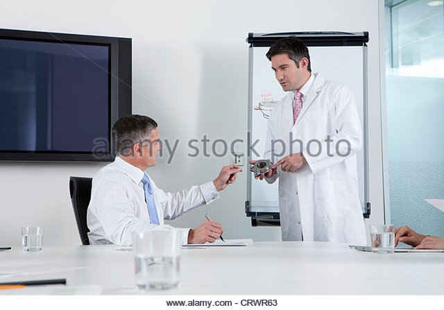 Engineer showing businessman machine part in conference room - Stock Image