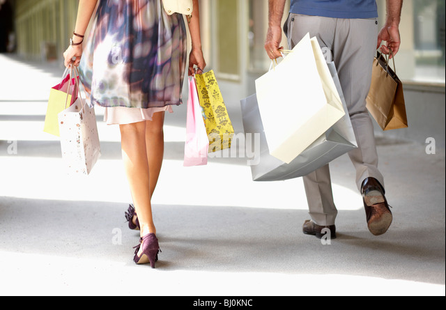 detail of couple carrying shopping bags - Stock Image