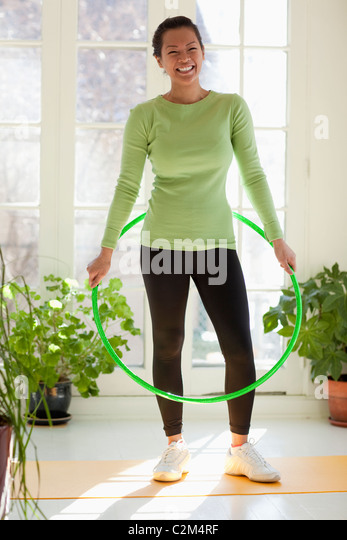 Smiling Asian woman exercising with hula hoop - Stock Image