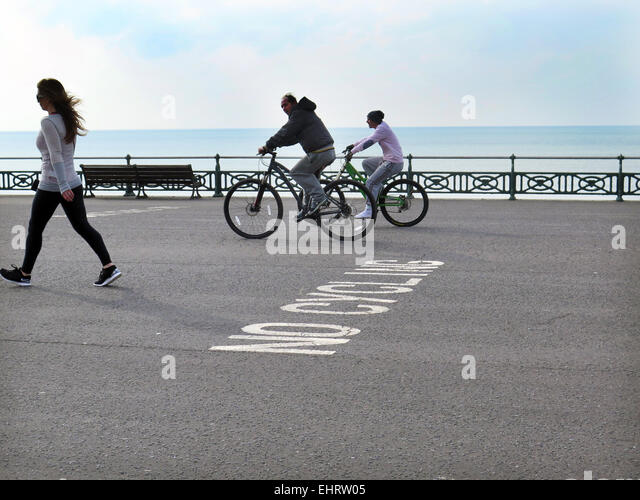 Two male Cyclists, not wearing crash helmets, ignore a NO CYCLING sign painted on the tarmac while cycling and looking - Stock Image