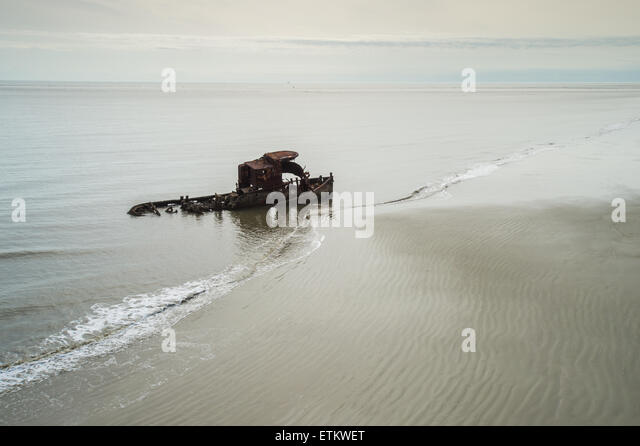 Rusty wreckage of old ship in beach water in Southeastern USA - Stock Image