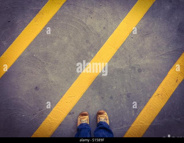 Dirty yellow shoes stand among the diagonal yellow stripes denoting the no parking zone of a concrete parkade. - Stock Image