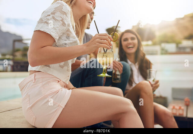 Cropped shot of young people sitting together hanging out with drinks. Partying on rooftop with focus on cocktail - Stock Image
