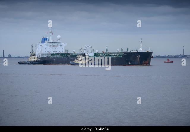 Tugboats pushing ship to harbor - Stock Image