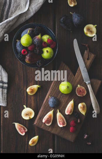 Figs on a wooden chopping board - Stock Image