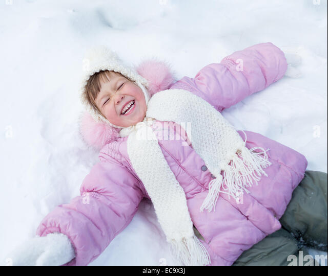 Happy kid lying on snow in winter outdoor - Stock Image