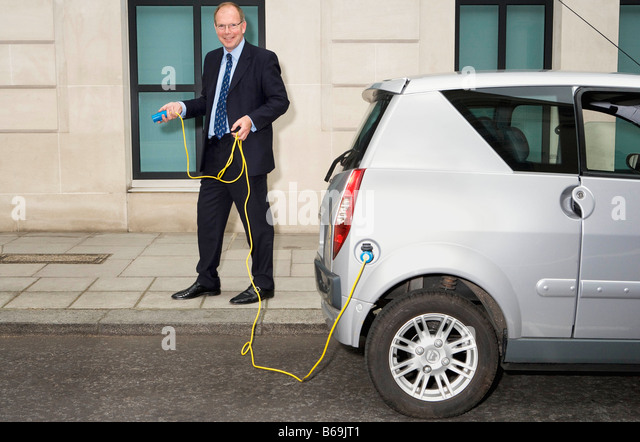 Man holding cable for electric car - Stock Image