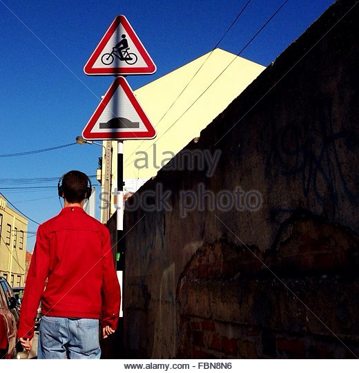 Rear View Of Man Walking By Road Signs In City Against Clear Blue Sky - Stock Image