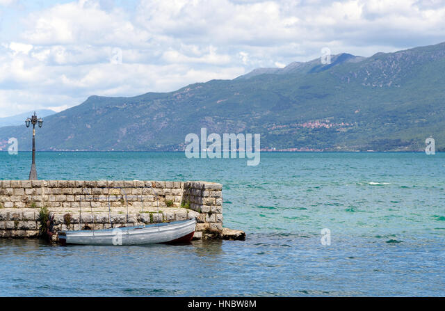Small white rowing-boat moored by the stone pier in the harbor at Ohrid lake, Macedonia - Stock Image