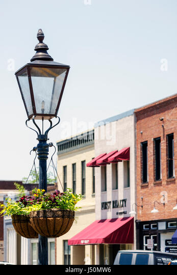 Alabama Greenville Commerce Street historic buildings business district lamppost hanging basket flowers - Stock Image