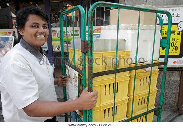 Japan Tokyo Shinjuku Asian man delivering rolling cart smiling - Stock Image