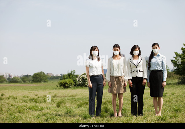 Businesswoman wearing pollution masks in field - Stock Image