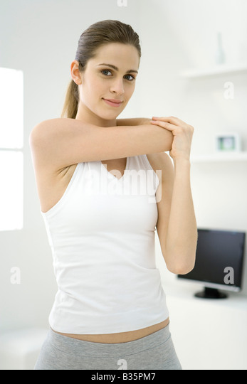 Woman stretching her arm, smiling at camera - Stock-Bilder