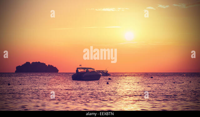 Vintage filtered silhouette of a little island and small boat at sunset. - Stock Image