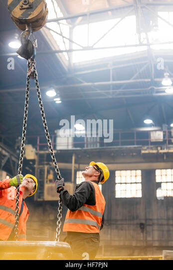 Steel workers looking up at crane chain in factory - Stock Image