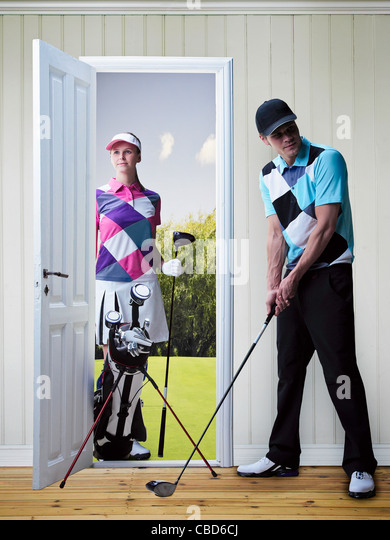 Couple playing golf in new home - Stock Image