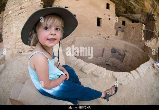 A young girl rests on a stone wall while exploring ruins in Mesa Verde National Park, Cortez, Colorado. - Stock Image