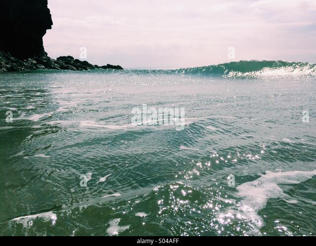 A rocky headland in Cornwall with a wave breaking on a sunny day in the sea. - Stock Image