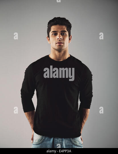 Portrait of handsome young hispanic guy posing. Smart male fashion model posing on grey background. - Stock Image