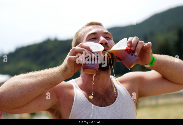 Guy drinking two beers at an outdoor concert - Stock Image
