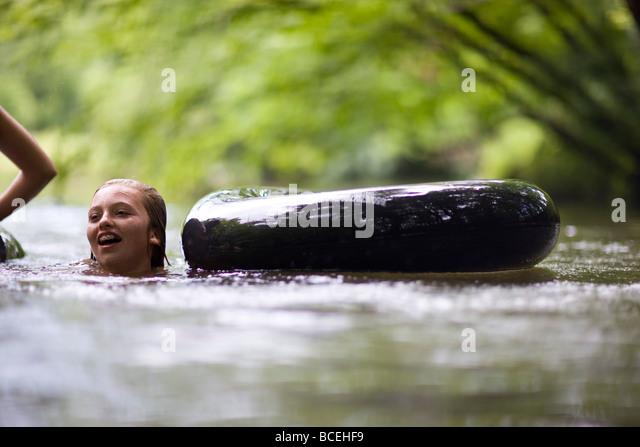 Teenagers having fun in innertubes in the water - Stock Image
