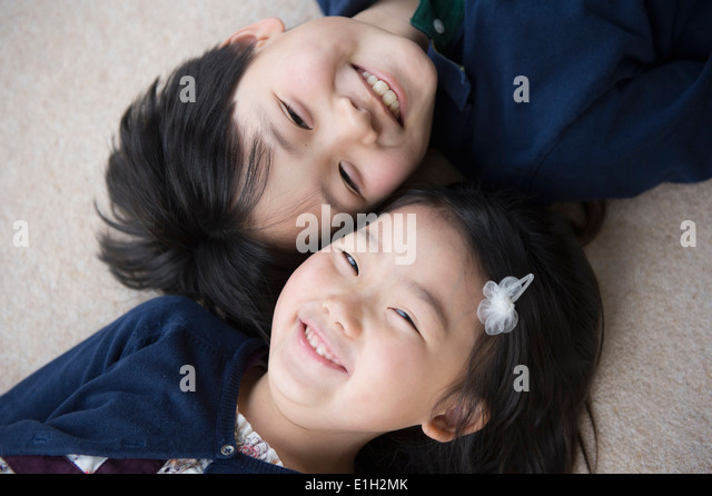 Portrait of brother and sister lying on carpet - Stock-Bilder