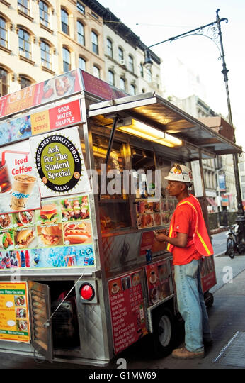 Construction worker ordering from a food truck in New York City - Stock Image