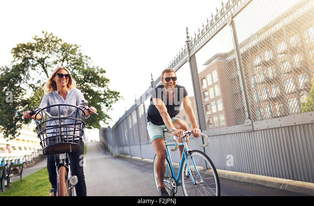 Young couple cycling in an urban park as they enjoy a healthy outdoor lifestyle in the fresh air and summer sun - Stock Image
