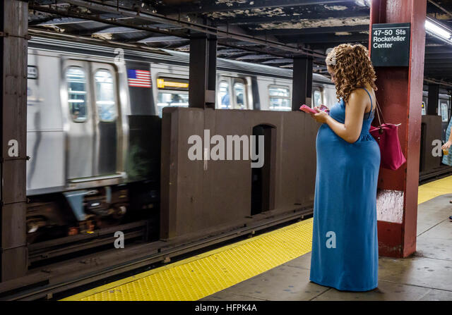Manhattan New York City NYC NY subway MTA public transportation Rockefeller Center station train platform woman - Stock Image