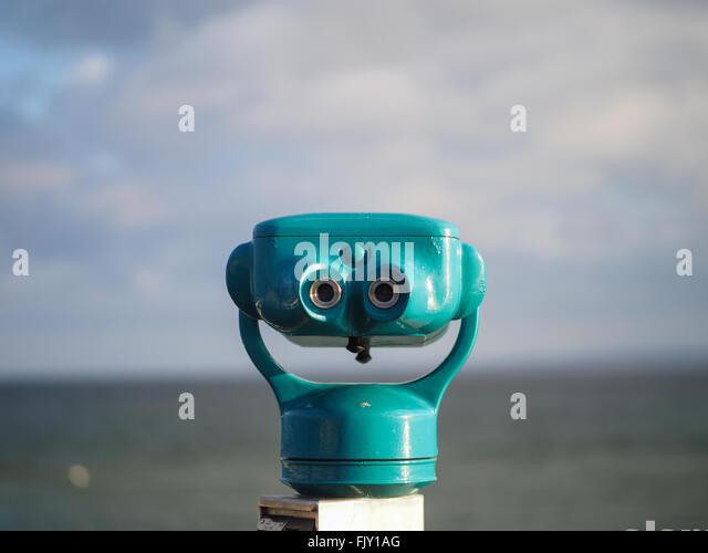 Close-Up Of Blue Coin-Operated Binoculars Against Sea On Sunny Day - Stock Image