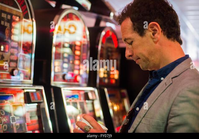 man gambling in casino with fruit machines losing money - Stock Image