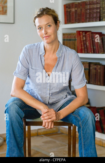 Mature woman sitting in chair, portrait - Stock Image