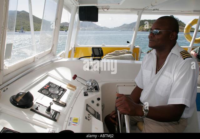 Sint Maarten Simpson Bay Lagoon Dutch Explorer Tour Boat Black male captain - Stock Image