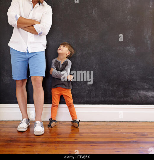 Indoor shot of little boy and his father standing with hands folded against black wall. Father and son looking at - Stock Image