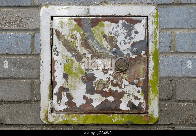 A green and gray corroded metal safe box with a lock built into a brick wall in Shoreditch,  Tower Hamlets, East - Stock Image