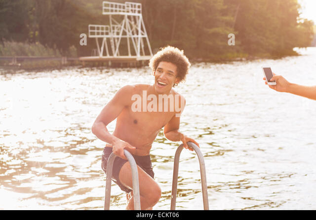 Cropped image of man photographing happy male friend coming out from lake - Stock Image