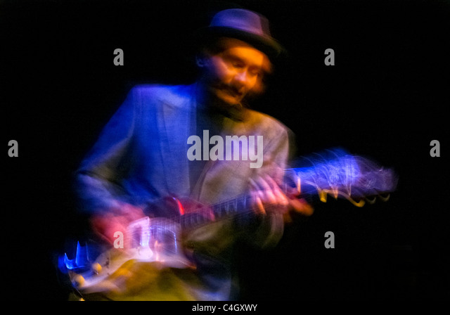 Man playing electric guitar, blurred with movement for a dynamic feel - Stock Image