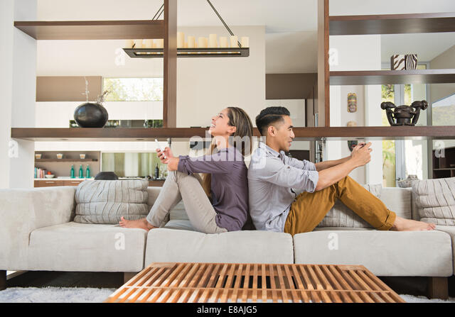 Couple sitting back to back playing games on smartphones on sitting room sofa - Stock Image