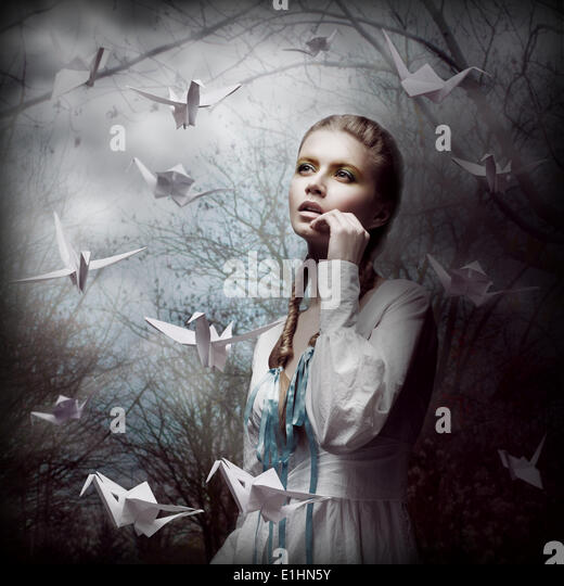 Inspiration. Woman with Flying White Origami Swans in Dark Mystic Forest - Stock Image