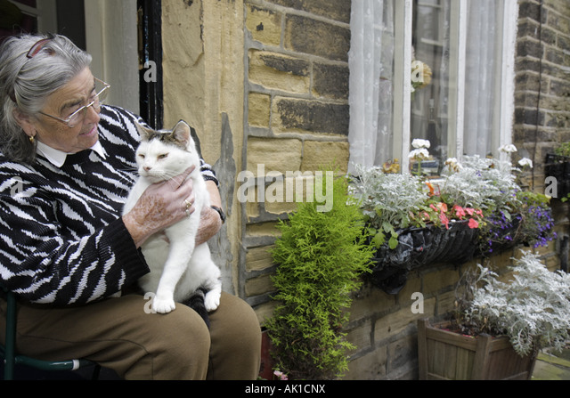 England UK Haworth Main Street woman cat - Stock Image