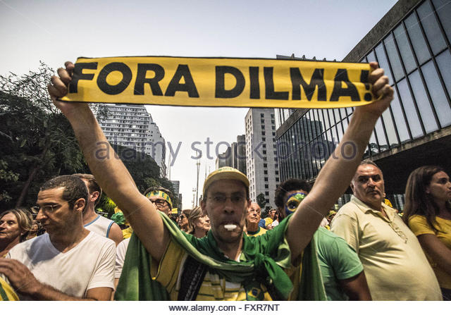 Sao Paulo, Brazil. 17th April, 2016. A man holds a placard which reads Dilma out! as thousands of activists supporting - Stock Image