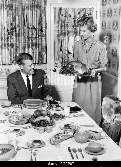 1950s THANKSGIVING FAMILY AT DINING ROOM TABLE MOM HOLDING TURKEY ON PLATTER PRINT CURTAINS TABLE SETTING WALLPAPER - Stock Image