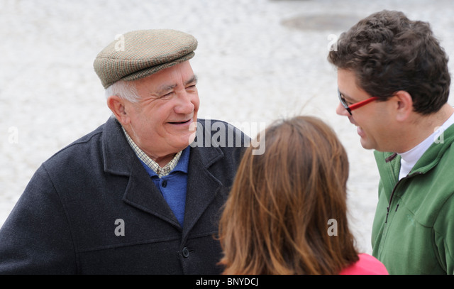 A senior male talking in the street to a couple in their 30´s Village life Aracena Andalucia Spain - Stock Image