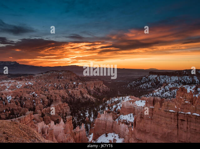 Snow Lingers on Bryce Canyon with Orange Sunrise Across Sky - Stock Image