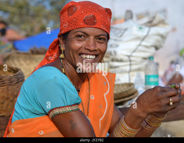 Closeup street portrait of a smiling mature Indian Adivasi market woman, peeling vegetable with both hands. - Stock Image