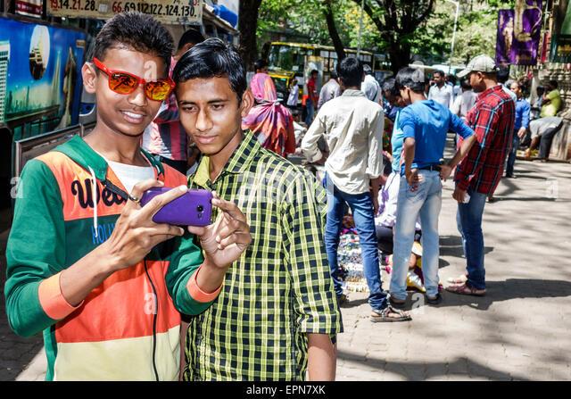 Mumbai India Asian Fort Mumbai Kala Ghoda Mahatma Gandhi Road teen boy man friends looking smartphone - Stock Image