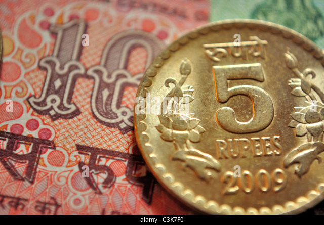 Indian currency, a coin of Rs. 5 and in the background a note of Rs. 10 - Stock-Bilder