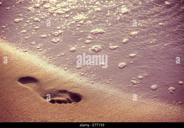 Retro picture of beach, water and footstep at sunset. - Stock Image
