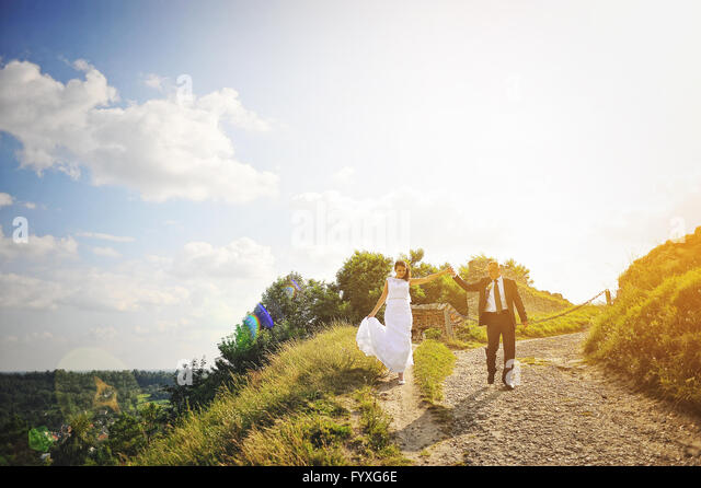 Newlyweds holding hands at the sunset - Stock Image