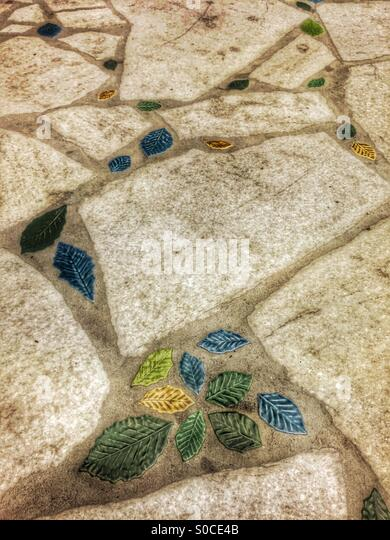 Pavement with natural stone slabs and green, blue and yellow leaf decorative accents. - Stock Image